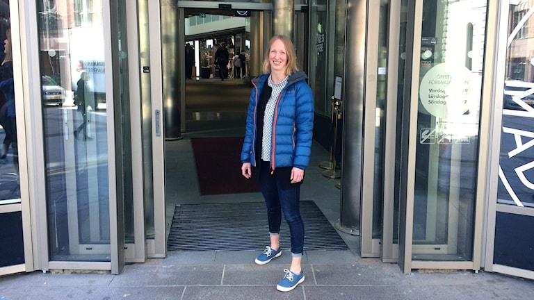 Sofia Stensson står i entrén till en galleria där man har skjutdörrar.