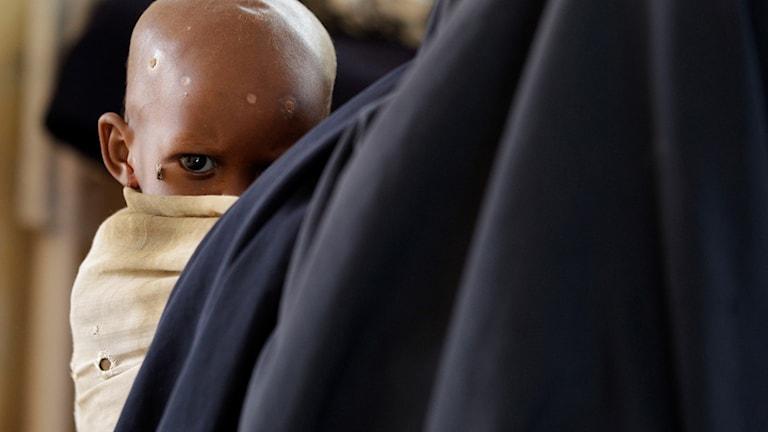 Ansiktet av ett litet barn skymtar fram bakom en axel.