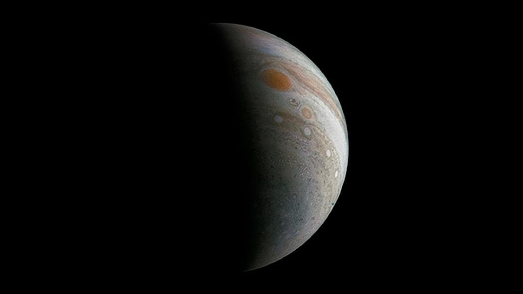 Planeten Jupiter mot svart bakgrund och belyst på ena sidan som en halvmåne.