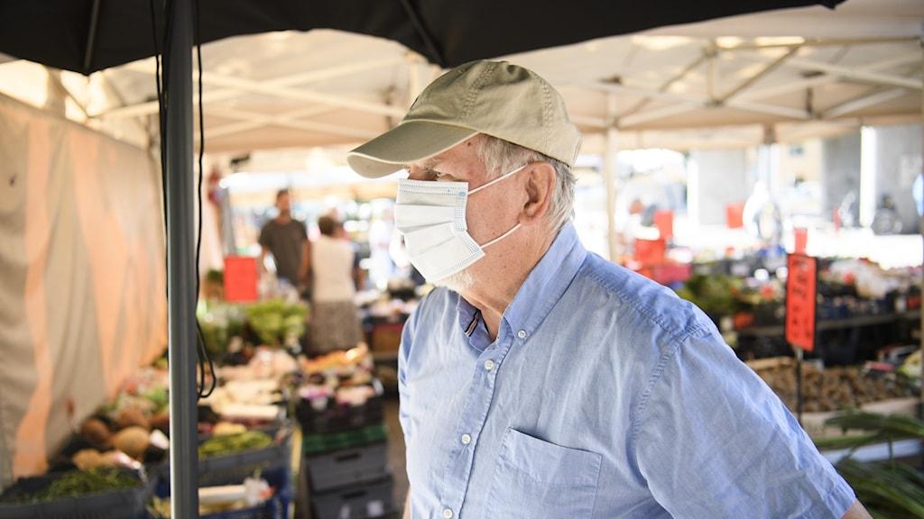 Äldre man med munskydd.