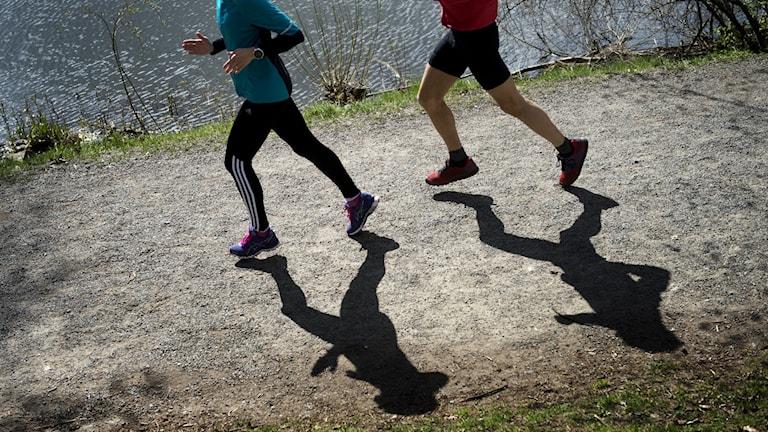 Två personer joggar på en grusväg.