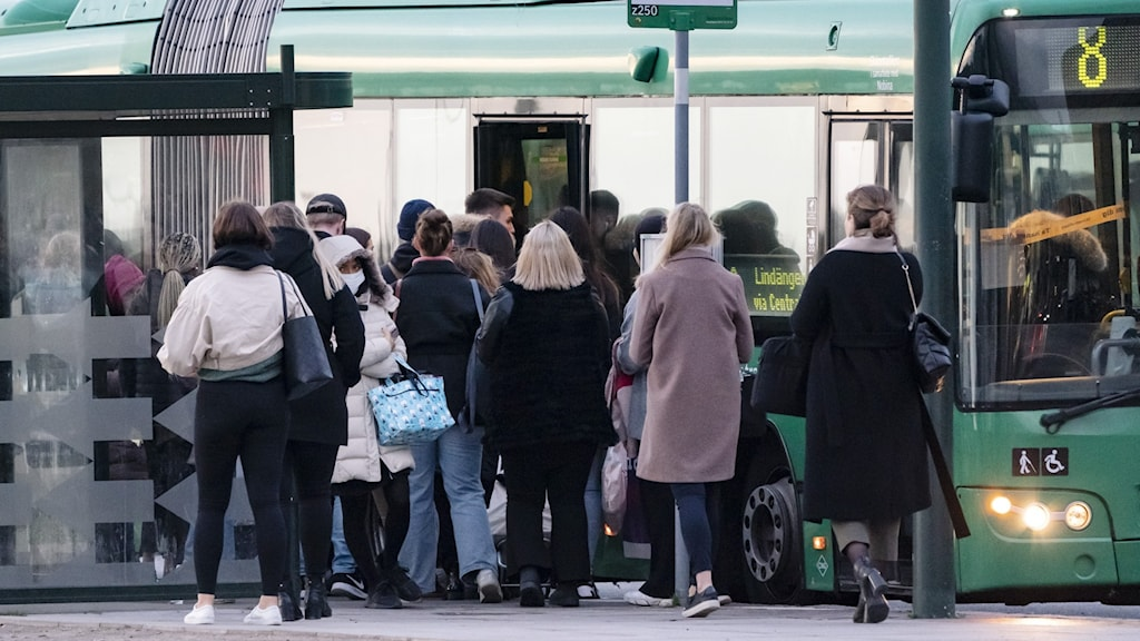 Flera personer som står nära varandra och väntar på att kliva på en buss.