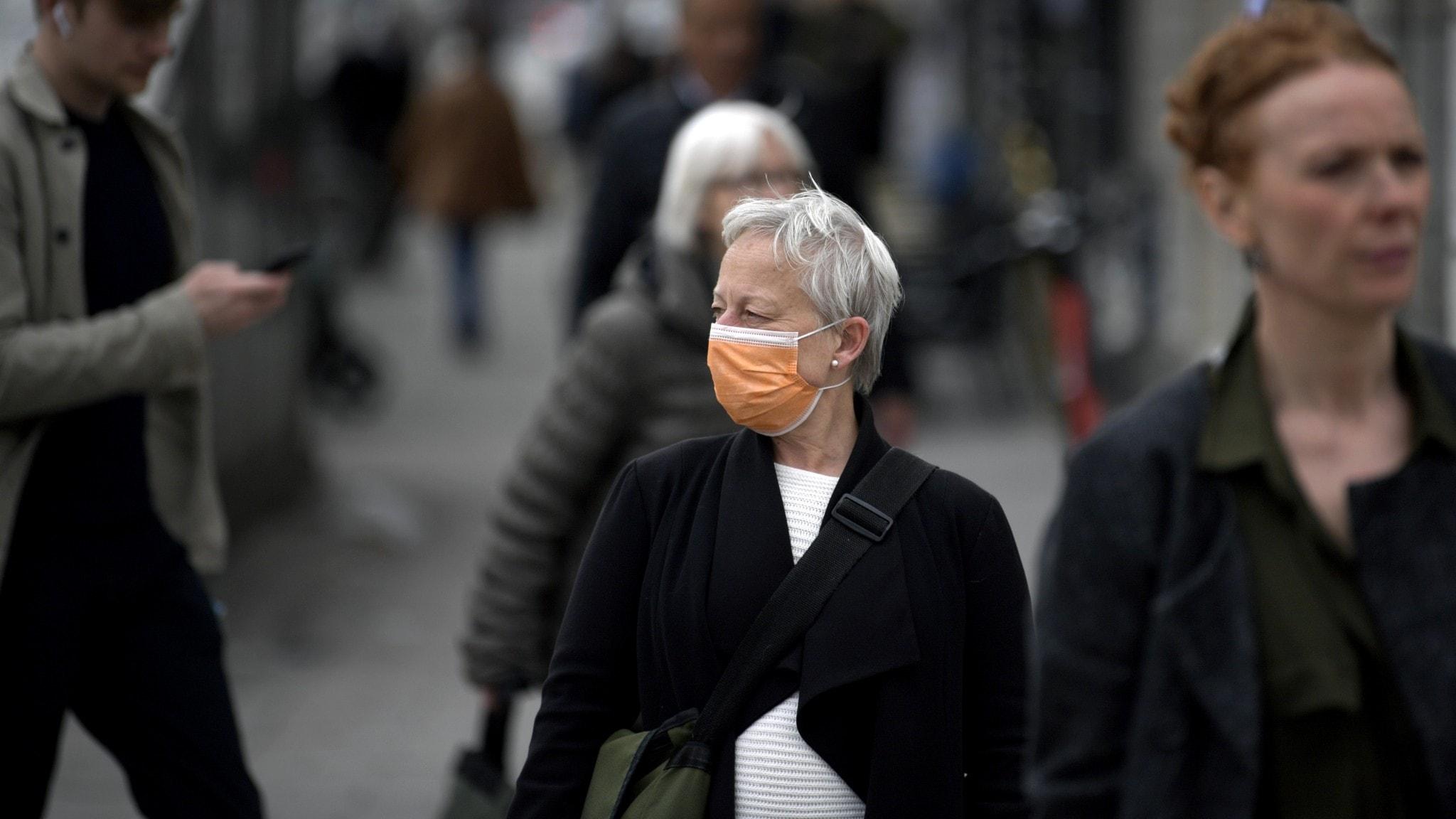 Kvinna bär munskydd när hon går på stan.