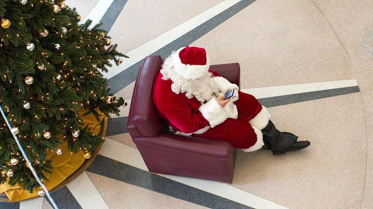En jultomte sitter i en fåtölj och surfar på sin mobil.