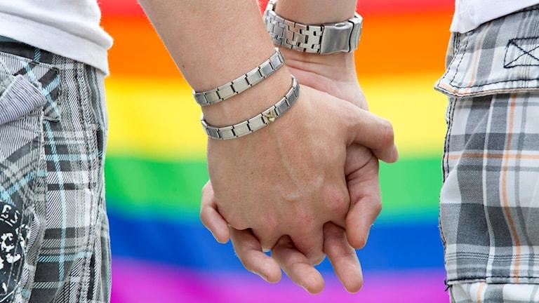 Närbild på händerna hos två män som håller varandra i handen med en regnbågsflagga i bakgrunden.