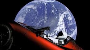En röd bil färdas i rymden. I förarsätet sitter en docka med austronaututrustning.