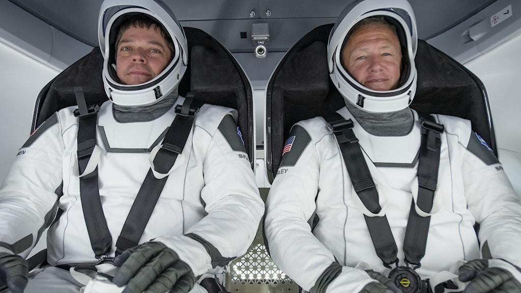 Två män i vita rymddräkter sitter fastspända i säten och ser mot kameran.