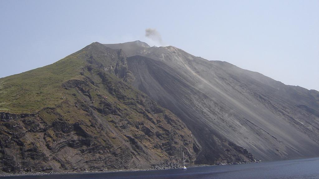 Vulkan med en rökpuff ovanför