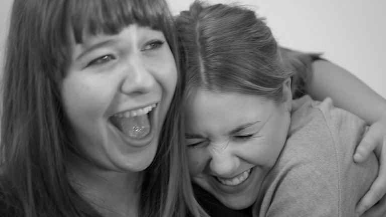 Två skrattande svenska kvinnor omfamnar varandra