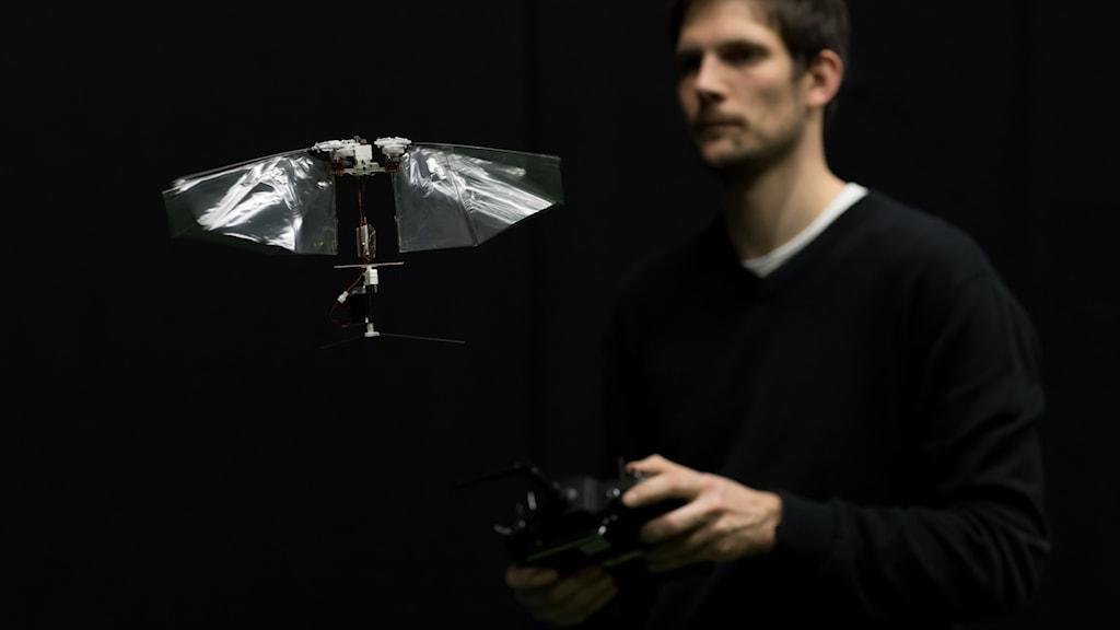 Forskaren Matej Karásek står i bakgrunden med en fjärrkontroll och styr en flygande liten robot i förgrunden.