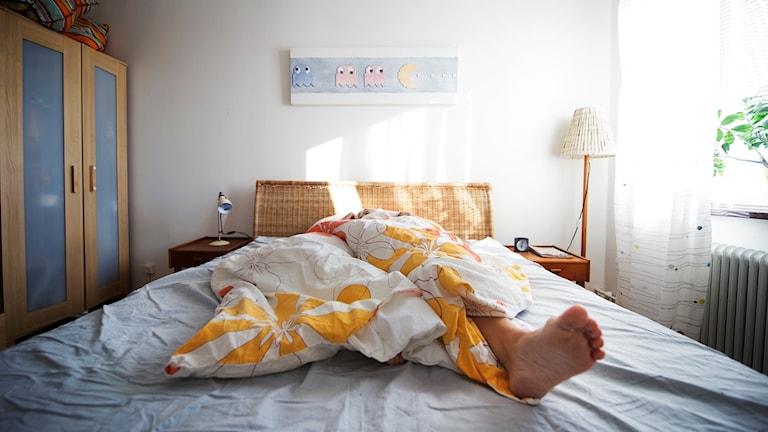 En säng där en fot sticker ut.