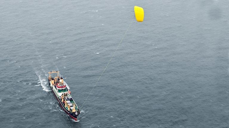 Flygbild på stort fartyg med en drake som hjälper till att dra fartyget.