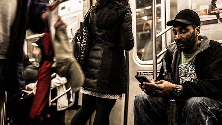 En man sitter och tittar i sin mobiltelefon. Han åker tunnelbana.
