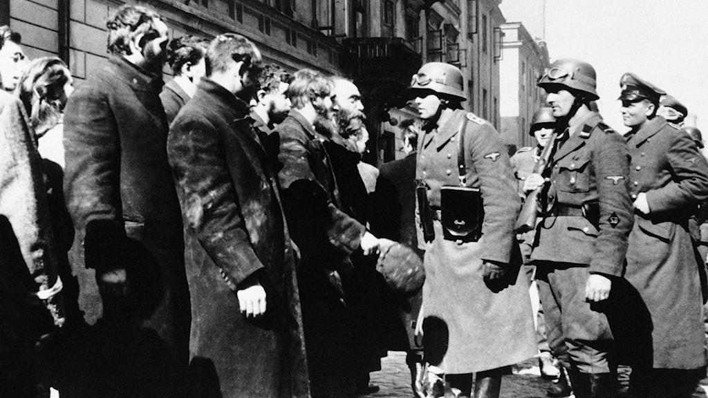 Svartvit bild där nazistiska officerare pratar med invånare i Warszawas ghetto.