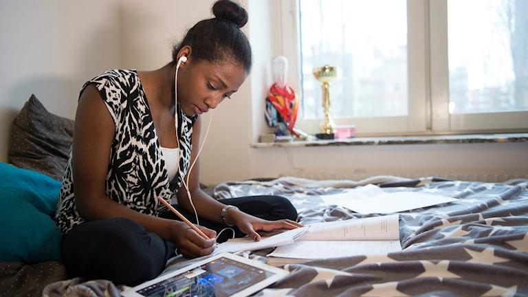 En mörkhyad 16-årig flicka lyssnar på musik och använder sin ipad i sängen på sitt rum samtidigt som hon gör sina läxor