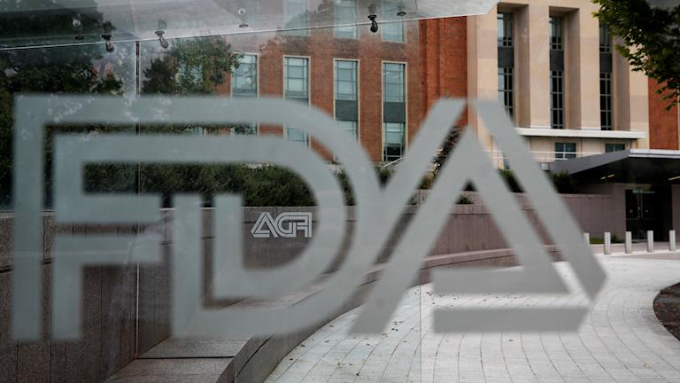 Logan på amerikanska läkemedelsverket FDA syns från en busshållplats framför en FDA byggnad.