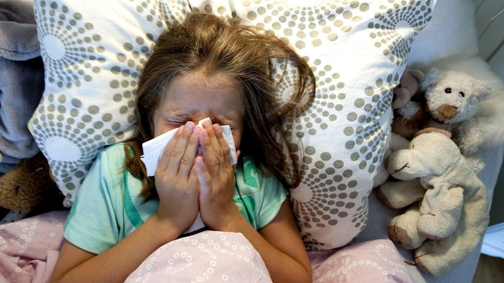 Barn som nyser i en servett i sin säng omgiven av gosedjur.