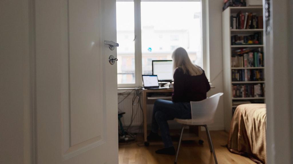 En kvinna sitter och jobbar i hemmiljö framför två dataskärmar