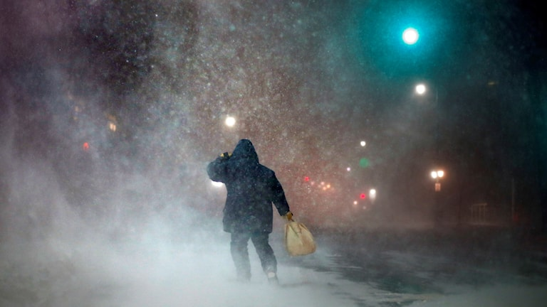 En person i blå jacka tar sig fram i snöstorm.