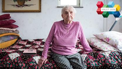 En äldre kvinna sitter i sin säng på ett äldreboende.