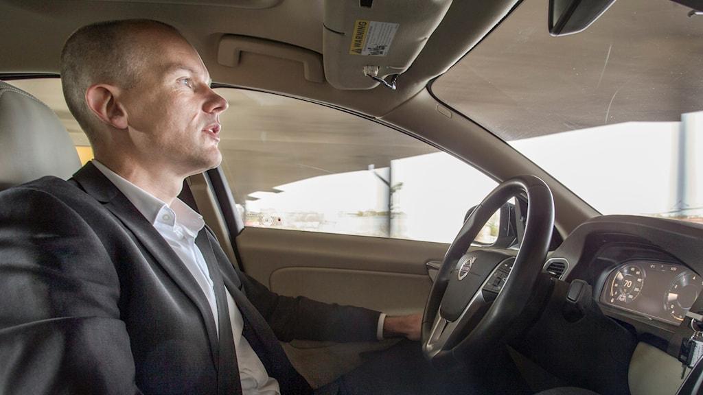 Förare utan händerna på ratten i självstyrande bil.