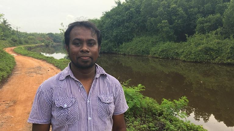 Sunanda Kodikara står på en grusväg, vid en flod med mangroveskog.