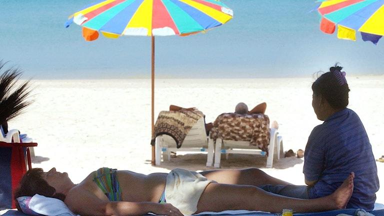 En västerländsk kvinnlig turist ligger på en strand i Thailand och får massage.