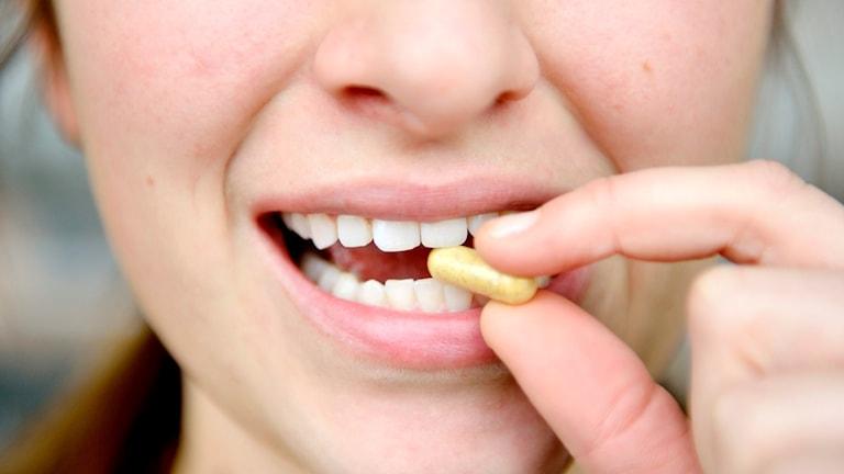 En kvinna stoppar in ett piller i munnen.