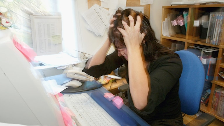 Stressad kvinna sliter sitt hår framför en dator hon sitter vid.