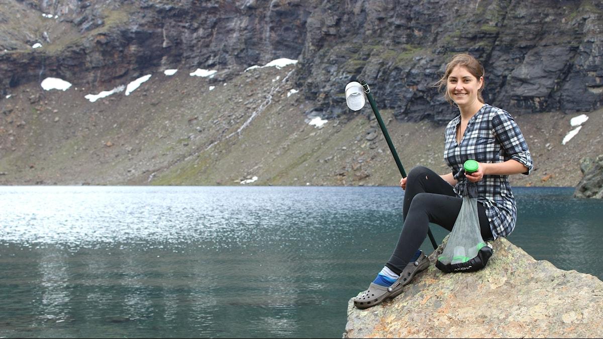 Biologen Sarah Atherton sitter vid en fjällsjö