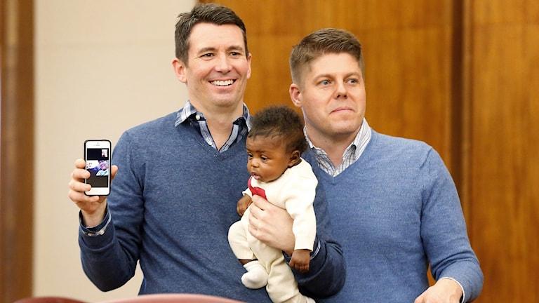 Två män med likadana blåa tröjor ler och håller en liten bebis mellan sig.