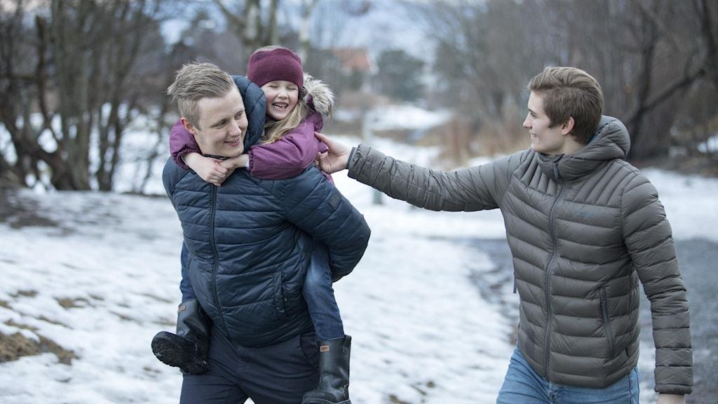 Familj är ute och går. De ser glada ut.