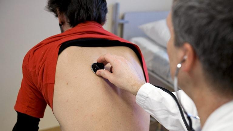 Person sitter vänd med ryggen mot kameran. Tröjan är uppdragen och en läkare lyssnar på lungorna med stetoskop.