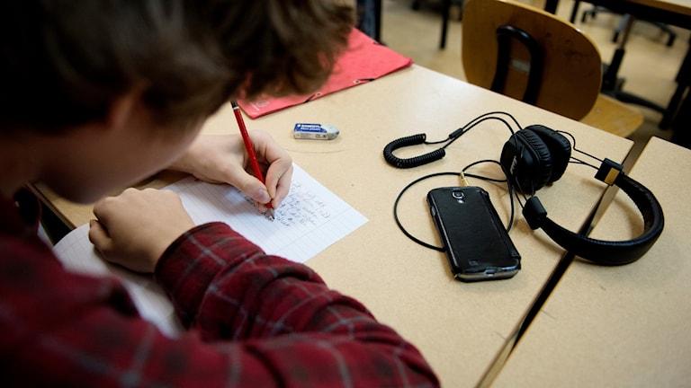 En högstadieelev sitter på en skolbänk och skriver med penna och papper.