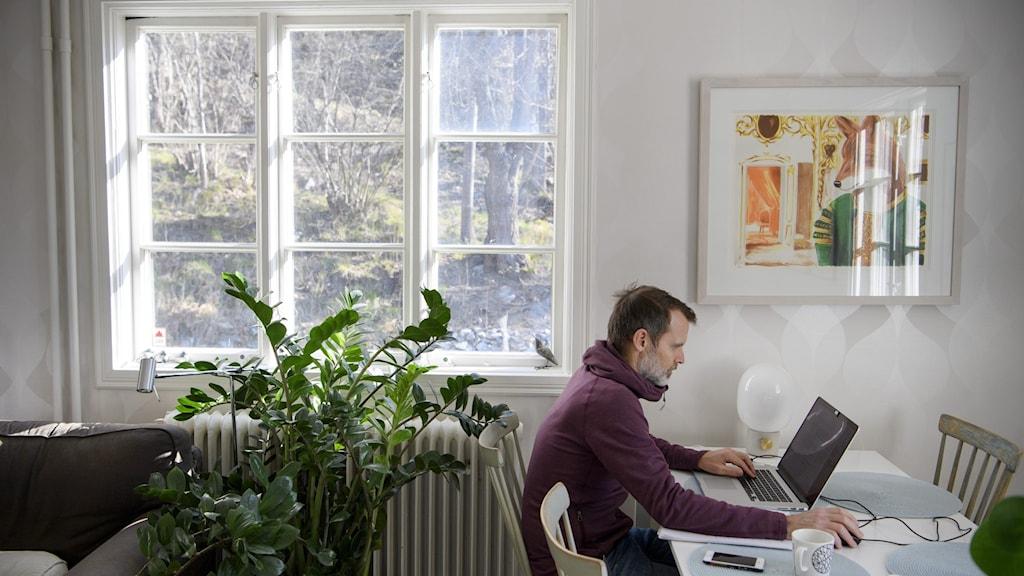 en person sitter och jobbar med sin dator vid köksbordet