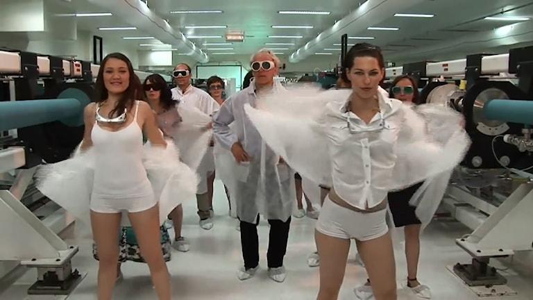 Fysikpristagaren Gérard Mourou omgiven av lättklädda kvinnliga studenter
