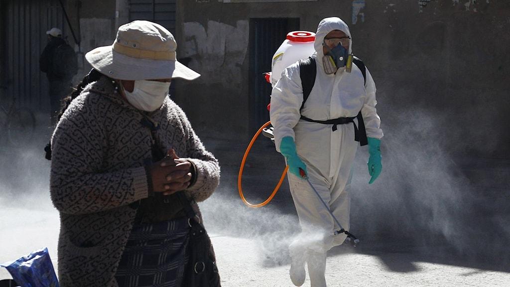 Person i skyddsutrustning sanerar en gata i Peru.