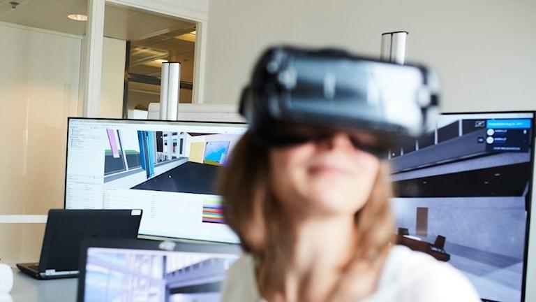 Person med VR-glasögon i kontorslandskap.