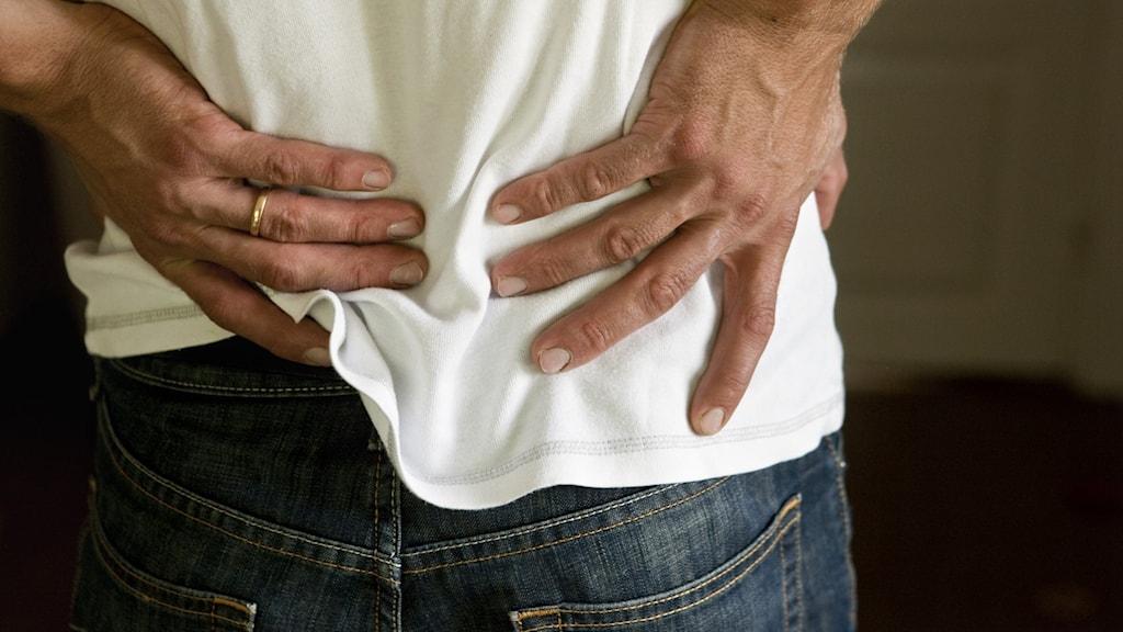 En person håller sig i ryggen och ser ut att ha ont.