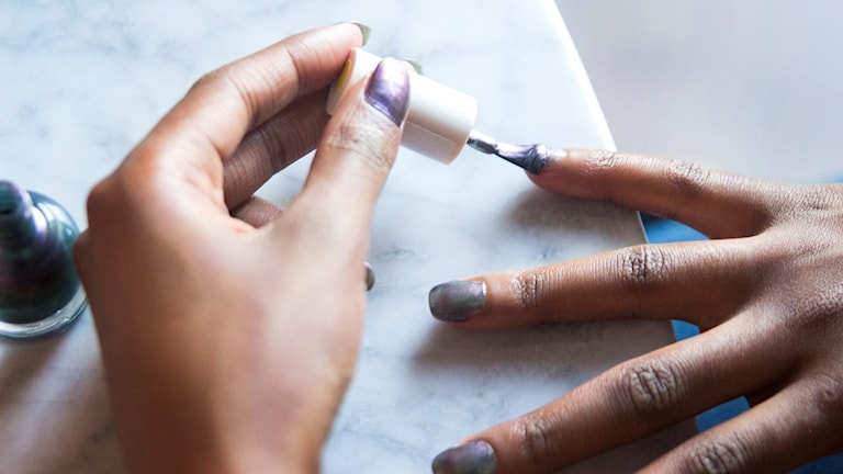 Kvinna målar nagellack.