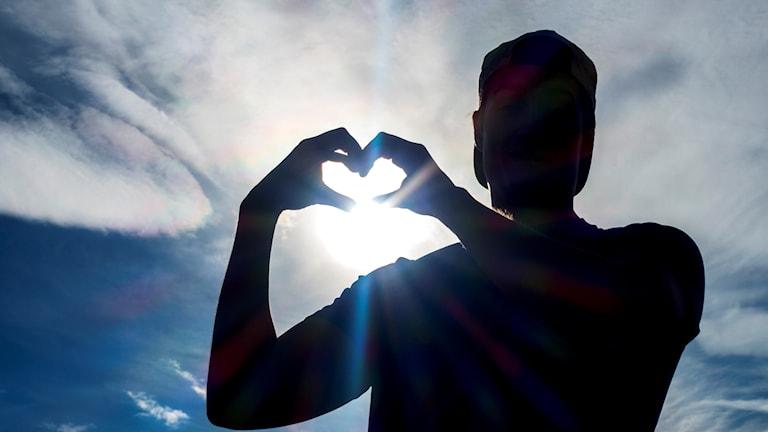 en man formar ett hjärta med händerna, i motsol. bara hans mörka siluett syns mot en blå, molning himmel.