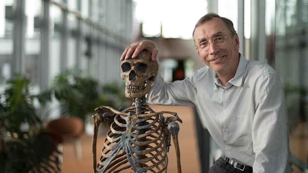 Svante Pääbo sitter bredvid ett skelett.