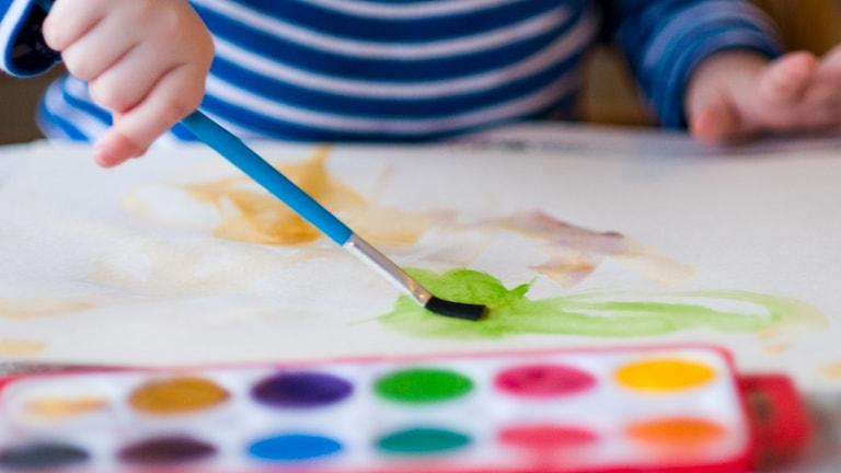 ett litet barn målar med vattenfärger