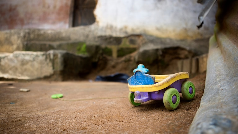 En leksaksbil står framför ingången till den lägenhet