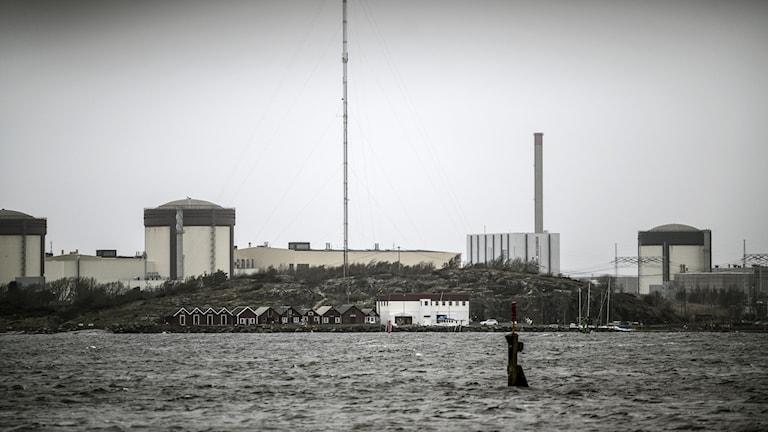 En bild i gråskala.Vatten förgrunden. I bakgrunden syns en stor anläggning som liknar någon form av fabrik.