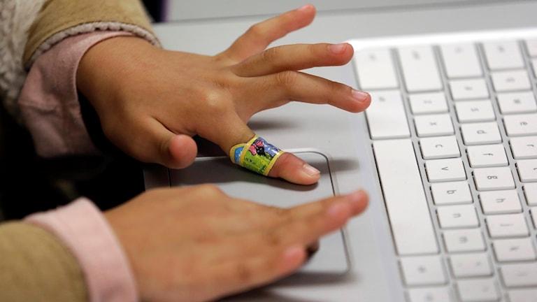 Barn använder dator på förskola.