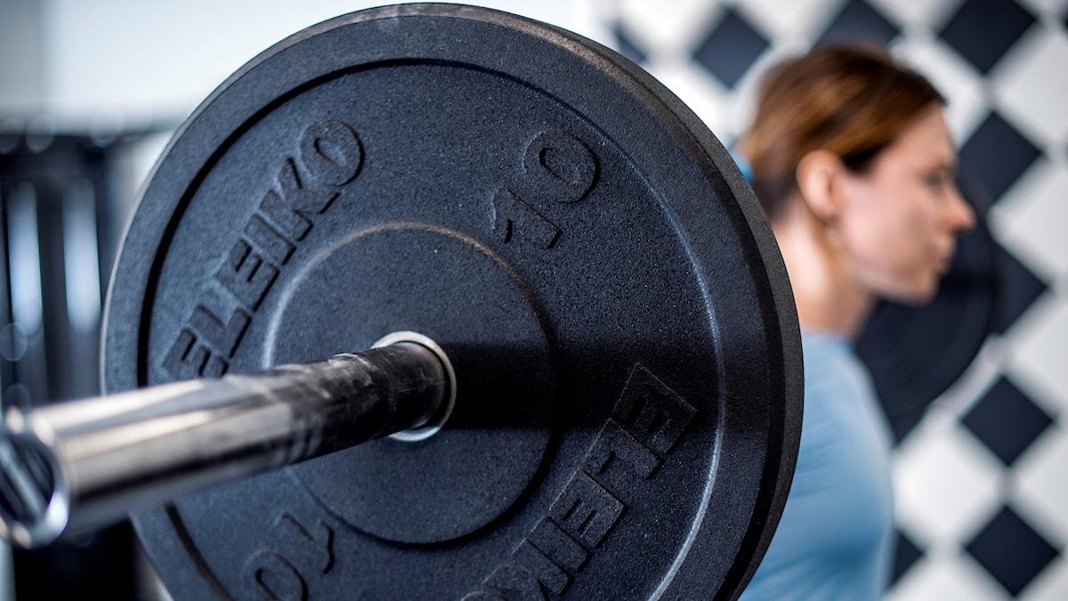 tjej lyfter vikter på stång