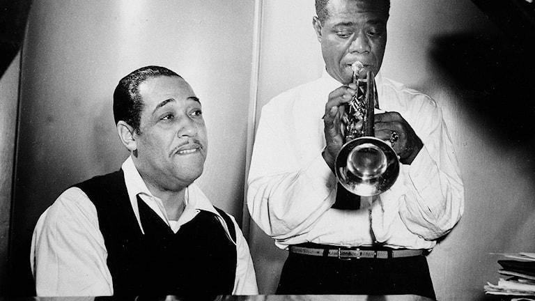Svartvit bild där Duke Ellington sitter ned vid piano och Louis Armstron står upp och spelar trumpet.