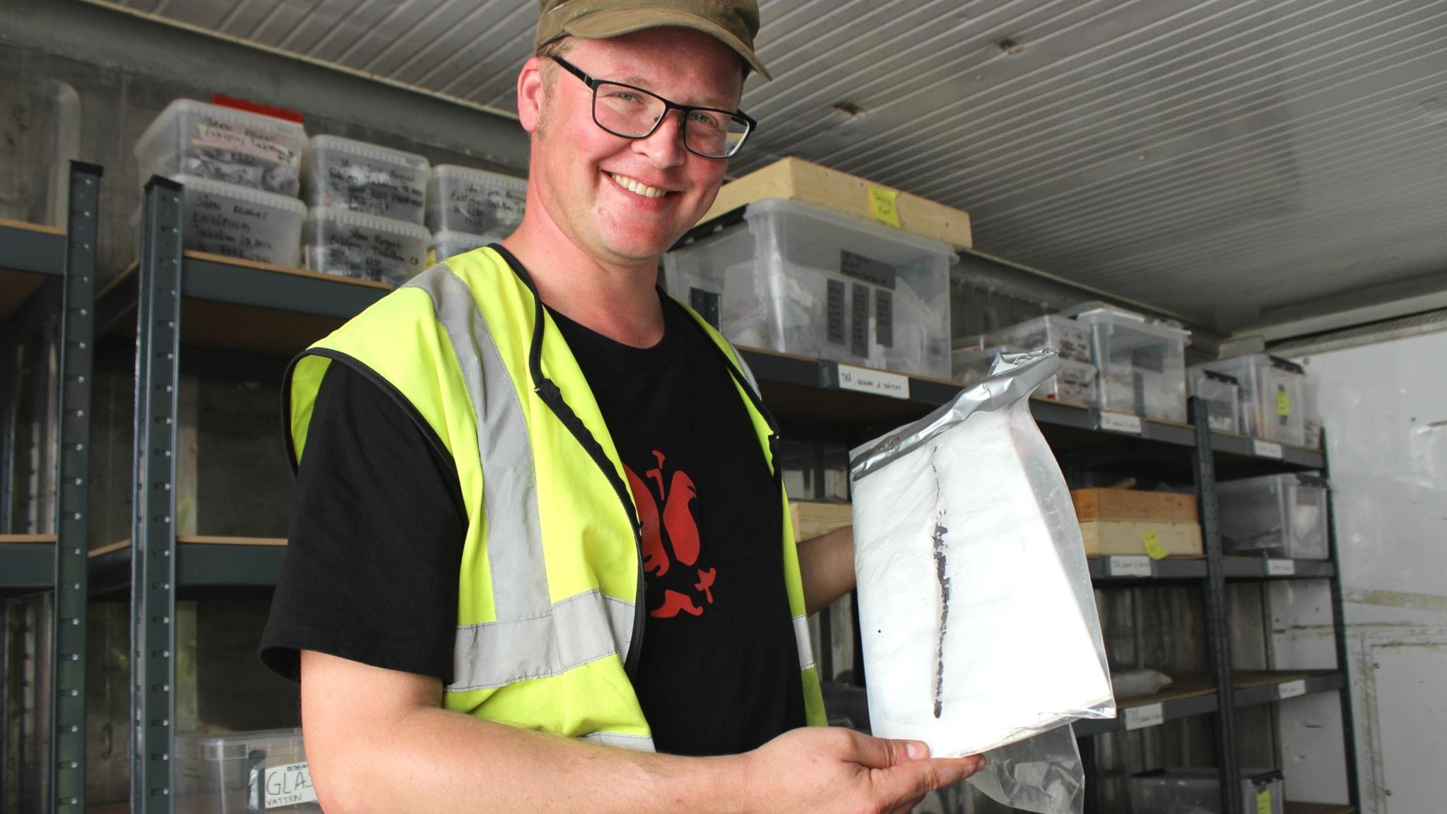 Arkeologen Joakim Kjellberg visar upp ett fynd från en utgrävning i Enköping som han antar är en barnleksak i form av en pilbåge.