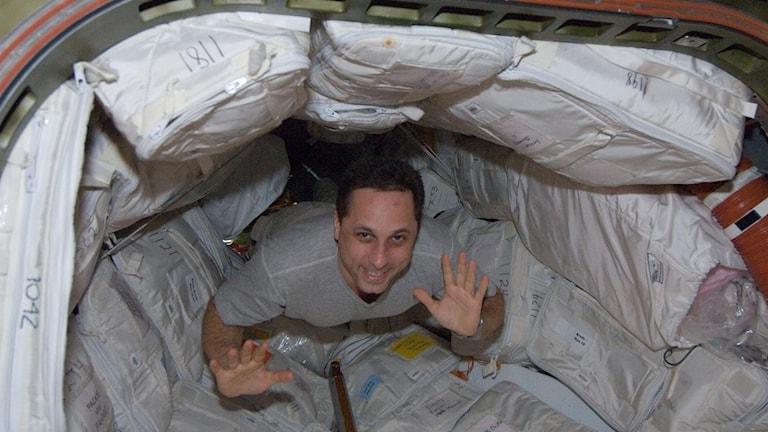 Kosmonauten Anton Shkaplerov svävar i tygndlöshet och vinkar i någon sorts tunnel på ISS.